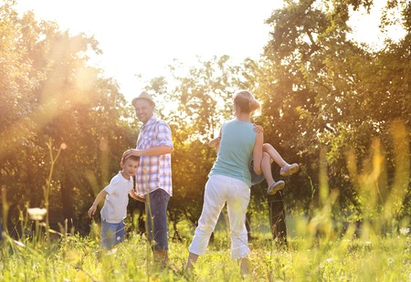 Happy young family spending time together outside in green nature. Reklamní fotografie