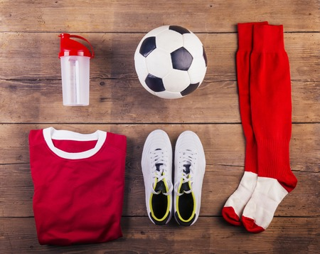 soccer cleats: Various football stuff lined up on a wooden floor background