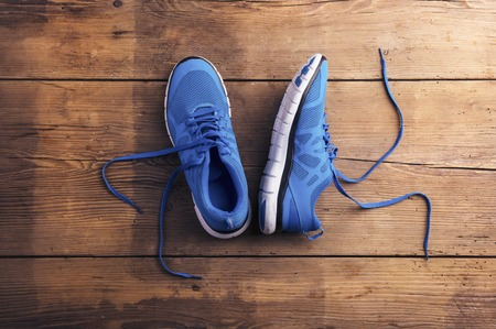 Pair of blue running shoes laid on a wooden floor background Archivio Fotografico