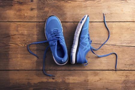 chaussure: Paire de chaussures de course bleues posées sur un plancher de fond en bois Banque d'images