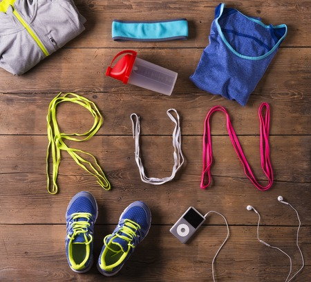 running shoes: Shoelaces run sign and various running stuff on a wooden floor background