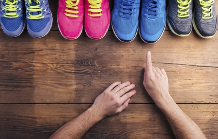 Four pairs of various running shoes laid on a wooden floor background Stock Photo