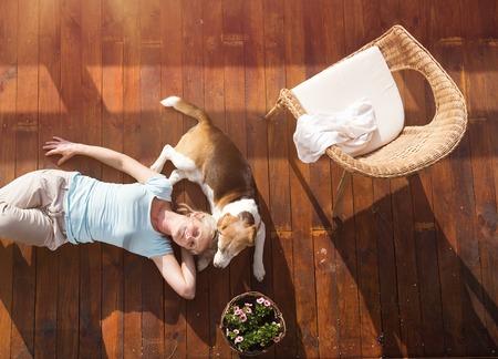 Starší žena se svým psem na terase svého domu.