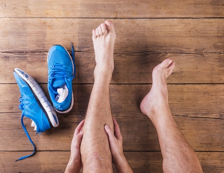 knee cap: Unrecognizable injured runner sitting on a wooden floor background Stock Photo