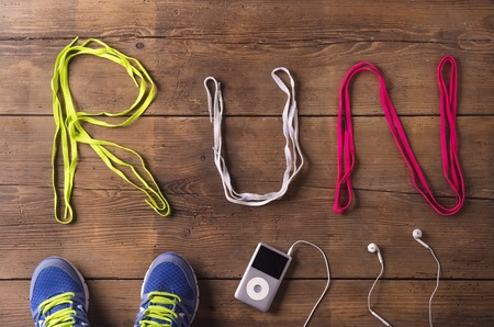 Shoelaces run sign, running shoes and mp3 player on a wooden floor background photo