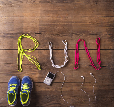 Shoelaces run sign, running shooes and mp3 player on a wooden floor background photo