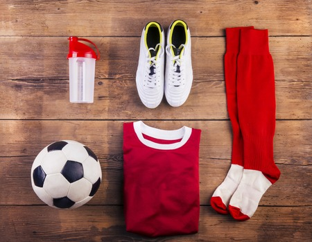 Various football stuff lined up on a wooden floor background photo