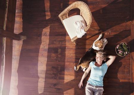 Haute femme avec son chien sur une terrasse de sa maison.