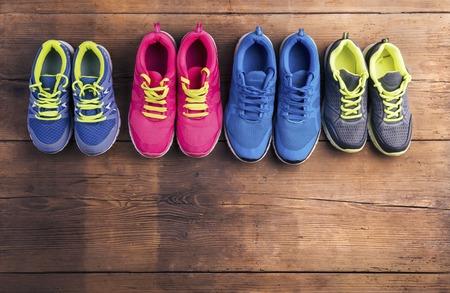 Vier paren van verschillende hardloopschoenen gelegd op een houten vloer achtergrond Stockfoto