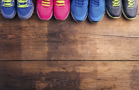 Four pairs of various running shoes laid on a wooden floor background Archivio Fotografico