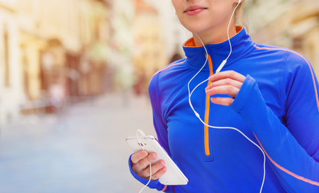 active listening: Beautiful young woman running in the city competition and listening to the music Stock Photo