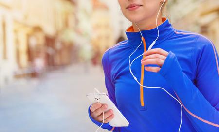 escucha activa: Joven y bella mujer corriendo en el concurso de la ciudad y la escucha de la m�sica