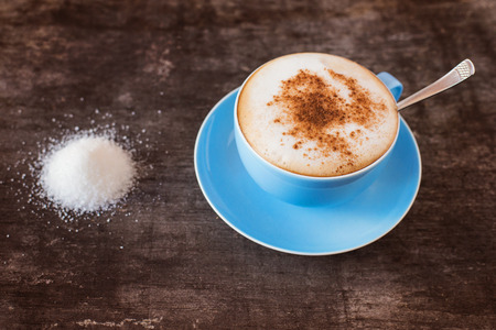 Cup of coffee and a heap of sugar on a wooden table background photo
