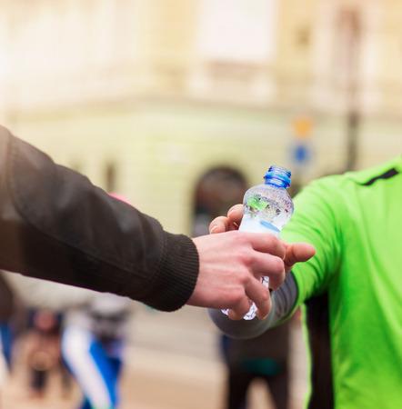 tomando refresco: Los corredores que toman una botella de agua en el punto de avituallamiento en la ciudad competici�n