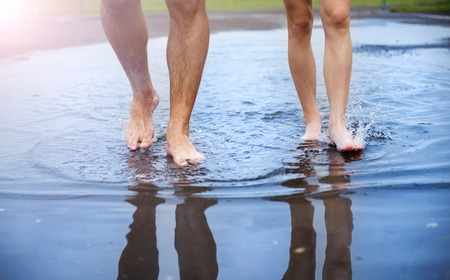 Unrecognizable woman and man walking barefoot through a puddle Imagens