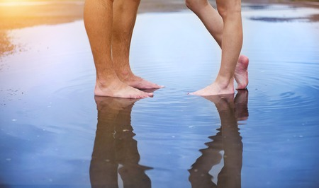 bare feet boys: Unrecognizable woman and man standing barefoot in a puddle Stock Photo