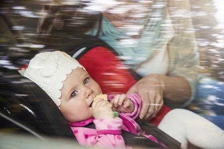 cinturón de seguridad: Madre en un coche, que tiene su pequeño bebé en un asiento para niños