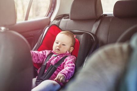 Mother driving a car, having her little baby girl in a child seat Stock Photo
