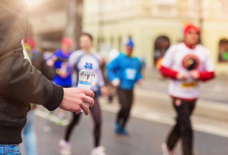 tomando refresco: Los corredores que toman una botella de agua en el punto de avituallamiento en la ciudad competición