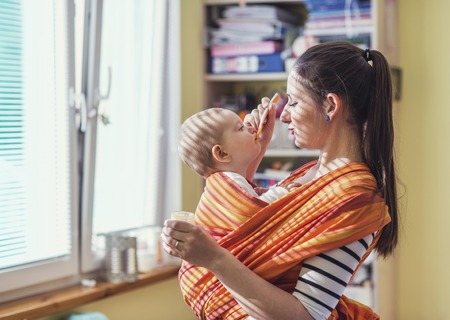 Young mother feeding her little daughter that she has in a baby carrier photo