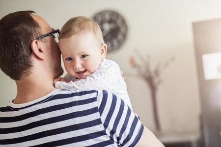 彼の腕の彼の娘を保持している若いパパ