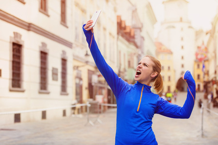 Beautiful young woman running in the city competition taking a selfie Stock Photo