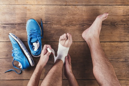 Unrecognizable injured runner sitting on a wooden floor background photo
