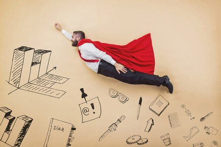 managers: Manager in a superman pose wearing a red cloak. Studio shot on a beige background.