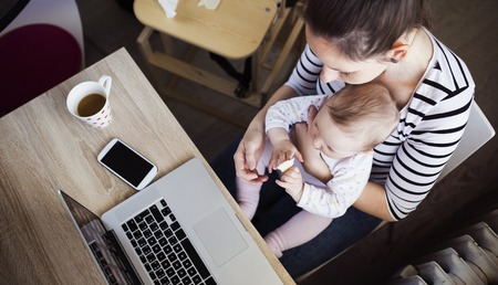 ホーム オフィス コンピューターと彼女の娘の若い母親