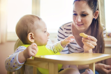 offspring: Young mother feeding her little daughter that is sitting in a high chair