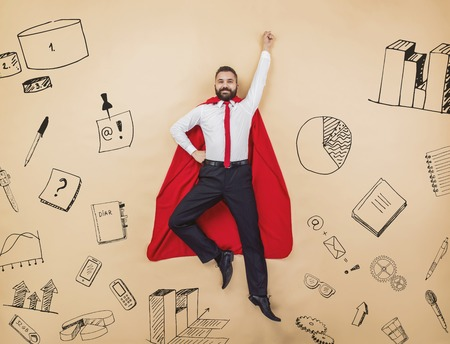 Manager in a superman pose wearing a red cloak. Studio shot on a beige background.
