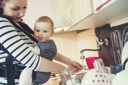 on tap: Young mother washing up dishes with her little daughter that she has in a baby carrier Stock Photo