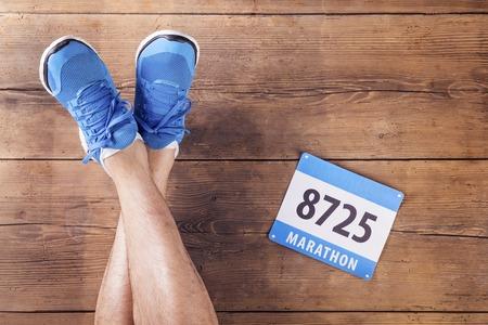 木製の床の背景にランナーとレース番号の足