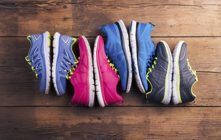 Four pairs of various running shoes laid on a wooden floor background Stockfoto