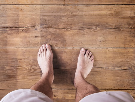 foot: Bare feet of a runner on a wooden floor background