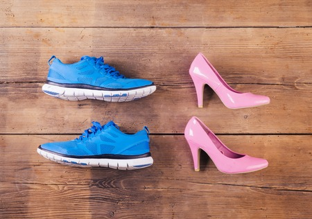 court shoes: Running shoes and pink court shoes on a wooden floor background Stock Photo