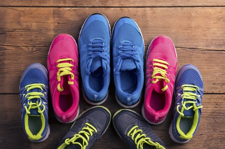 laid: Four pairs of various running shoes laid on a wooden floor background Stock Photo