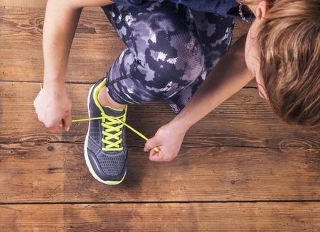 Unrecognizable young runner tying her shoelaces. Studio shot on wooden floor background. photo