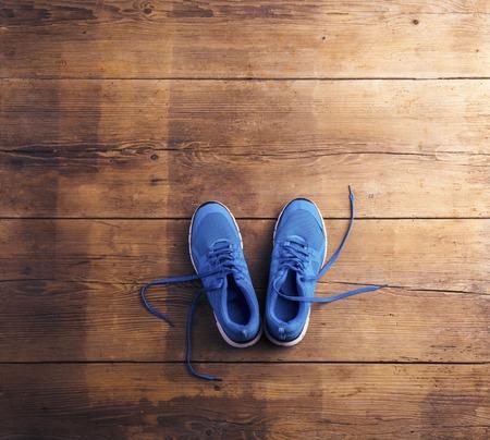 木製の床の背景にブルーのランニング シューズのペアを置いた