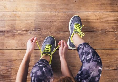 라이프 스타일: 그녀의 신발 끈을 묶는 인식 할 수없는 젊은 주자입니다. 스튜디오 나무 바닥 배경에 총. 스톡 콘텐츠