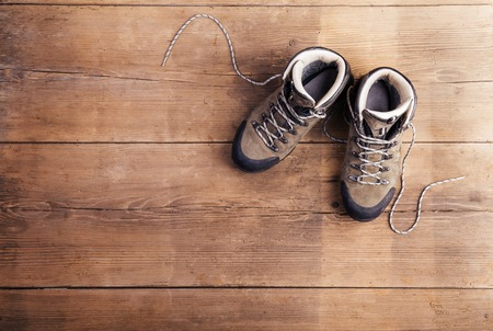 relaxation background: Hiking shoes laid on a wooden floor background