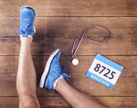 木製の床の背景にランナー、メダル、レース番号の足 写真素材