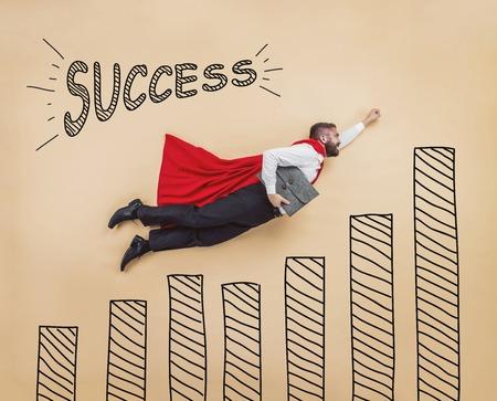 Manager in een superman pose dragen van een rode mantel. Studio opname op een beige achtergrond.