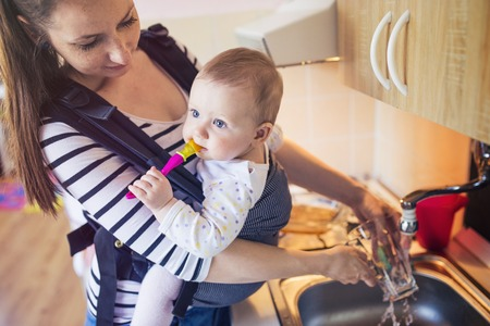 baby carrier: Young mother washing up dishes with her little daughter that she has in a baby carrier Stock Photo