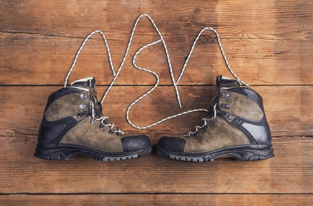 outdoor pursuit: Hiking shoes laid on a wooden floor background