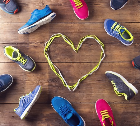 youth sports: Various running shoes laid on a wooden floor background