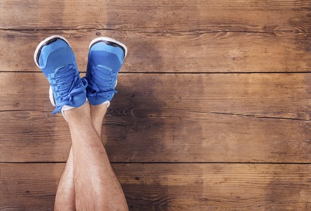 crossed legs: Legs of a runner on a wooden floor background