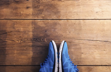 laid: Pair of blue running shoes laid on a wooden floor background Stock Photo