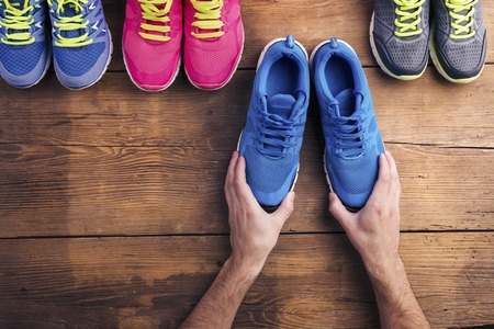 shoes: Four pairs of various running shoes laid on a wooden floor background Stock Photo