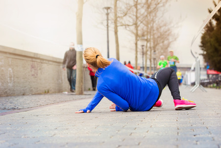 fitness motivation: Young woman running in the city competition falling on the ground
